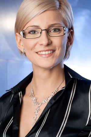 dark glasses: Indoor portrait of happy young businesswoman standing on office corridor, smiling.