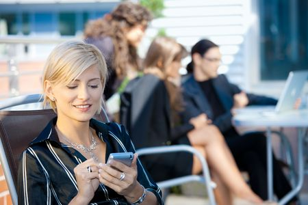 officetower: Young businesswoman using smart mobile phone, outside office building.