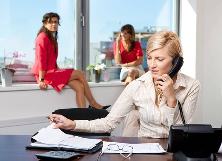 Young businesswoman sitting at desk in office, talking on landline phone, looking at personal organizer. photo