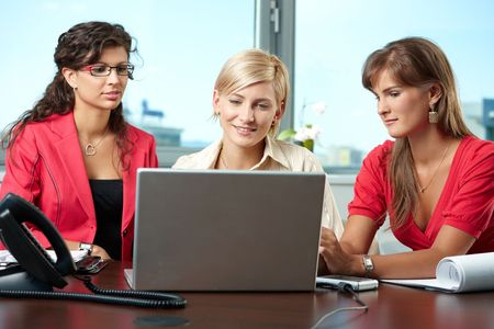 cooperating: Attractive businesswomen sitting at table in meeting room, using laptop computer, smiling. Stock Photo