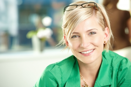 young adults: Closeup portrait of attractive young businesswoman wearing green shirt, smiling.