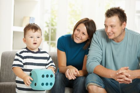 Little boy playing with big toy die, happy parents watching from background. Stock Photo - 6438334
