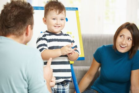 Father, mother and boy child playing together with toy whiteboard, letters and numbers. Stock Photo - 6438108