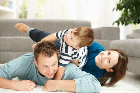 recreation room: Happy family playing at home, lying heaped on floor in living room. Stock Photo