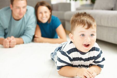 Happy family lying on floor in living room. Selective focus on little boy. Stock Photo - 6438264