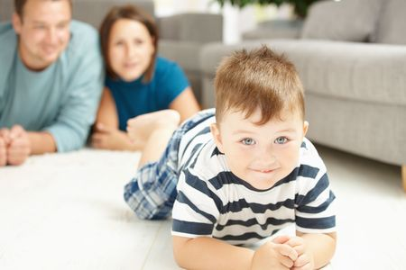 Happy family lying on floor in living room. Selective focus on little boy. Stock Photo - 6438159