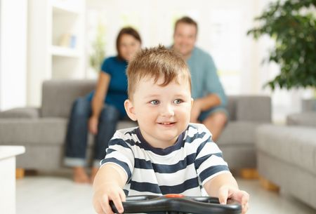 Happy little boy driving toy car his parents sitting on couch in background. Selective focus on child. photo