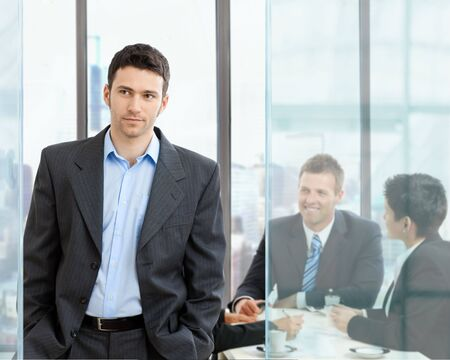 formal attire: Young businessman standing in modern glass office, businesspeople having a meeting in the background. Stock Photo