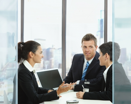 Young businesspeople having a business meeting in corporate office, using laptop computer. Copyspace on blank screen. Stock Photo - 6438332