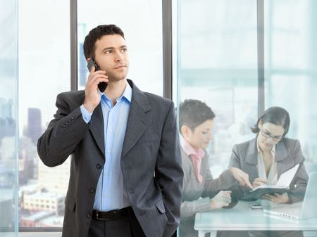 Businesswoman talking on mobile phone in modern office. Businesswomen working at desk in the background. photo