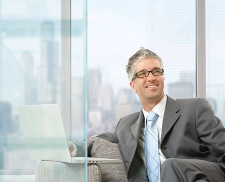 Happy businessman sitting on couch using laptop in modern glass office, smiling. photo