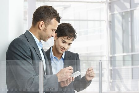 Two businesspeople standing in modern office building with glass walls, using smart mobile phone. Stock Photo - 6438259