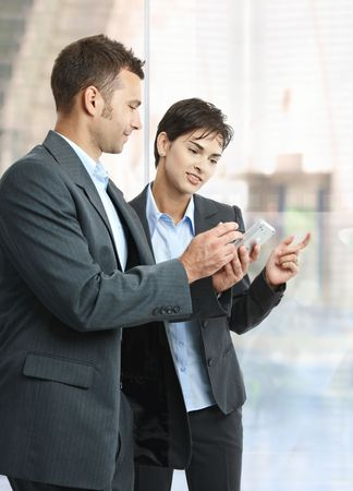 Two businesspeople standing in office lobby using smart mobile phone, smiling. Stock Photo - 6438153