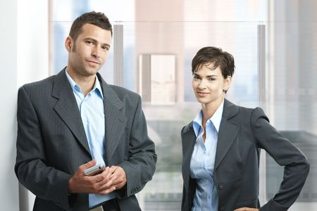 Two young businesspeople standing in modern office with glass walls, looking at camera, smiling. photo