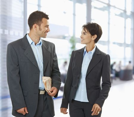 Two happy businesspeople talking in office lobby, looking at each other, smiling. photo