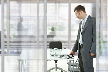 job satisfaction: Businessman leaving modern glass walled meeting room, picking up his notes and organizer.