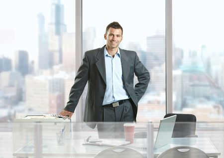 Happy businessman standing behind office desk, smiling. photo