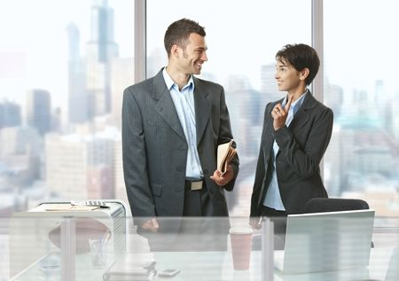 Two businesspeople standing at desk in front of windows in office, talking and smiling. Stock Photo - 6438093