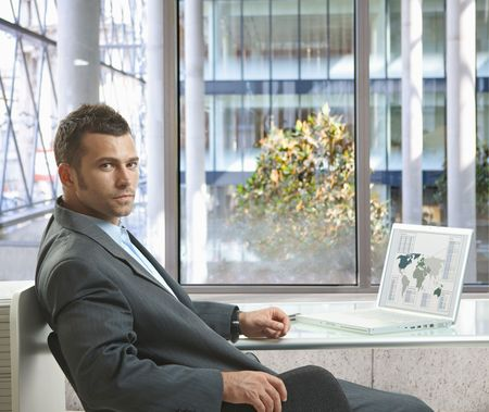 Serious businessman sitting at desk in office, working with laptop computer, looking back. photo