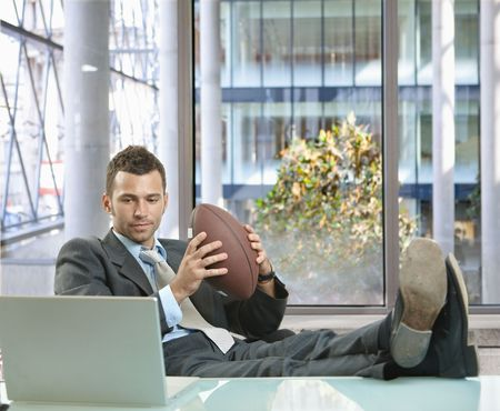 Relaxed businessman sitting at desk in front of office windows, holding football and smiling. photo