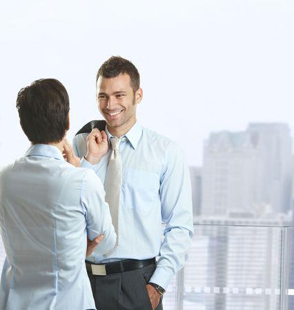 dos personas hablando: Dos empresarios de pie en el balc�n de la Oficina centro edificio, hablando y sonriente.
