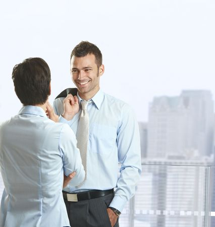 balcony window: Two businesspeople standing on balcony of downtown office building, talking and smiling.