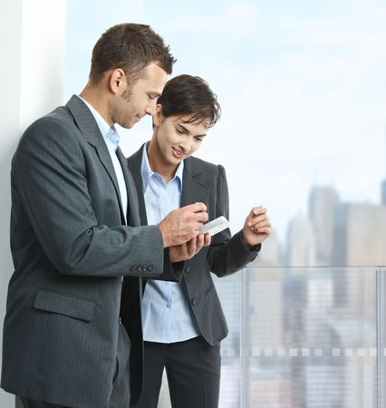 Two businesspeople standing on balcony of downtown office building, using smart mobile phone, smiling. photo