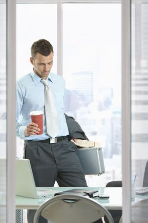 working attire: Businessman leaving office, holding suitcase and coffee cup in hand.