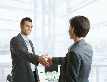 Smiling businessman greeting businesswoman with handshake before meeting. photo