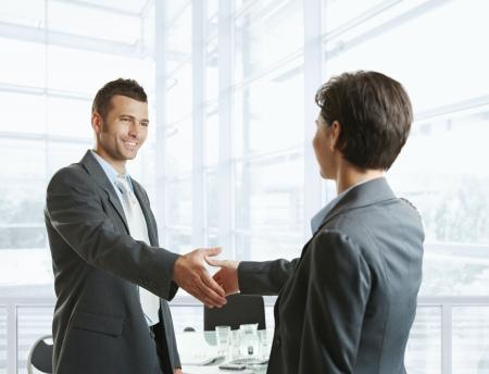 de bienvenida: Sonriendo empresario saludo a Empresaria con apret�n de manos antes de reuni�n. Foto de archivo