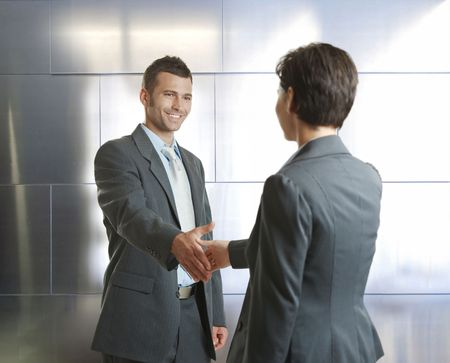 Smiling businessman and businesswoman shaking hands in modern design office. photo