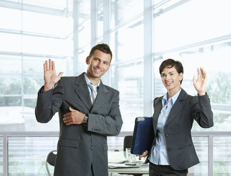 Businessman and businesswoman waving hands, greeting somebody before meeting. photo