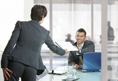 woman with document: Businesspeople working in office. Smiling businessman handing over documents to businesswoman.