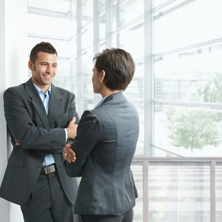 Two young businesspeople talking in office lobby, looking at each other, smiling. Stock Photo - 6438251