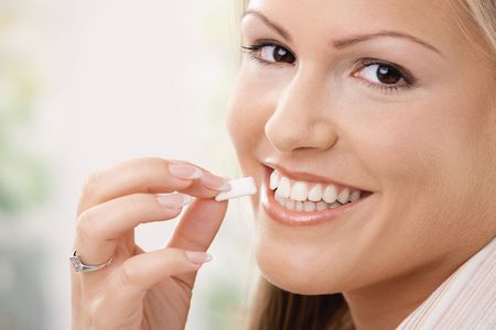 Beautiful young woman eating chewing gum, smiling.  photo