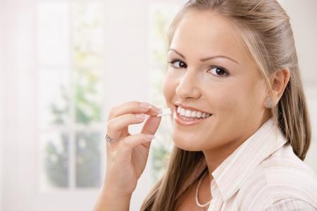-Guma do żucia: Piękne młoda kobieta jedzenia chewing gumy, uśmiech.  Zdjęcie Seryjne