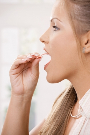 Closeup of youngl girl taking pink chewing gum. Side view portrait. photo