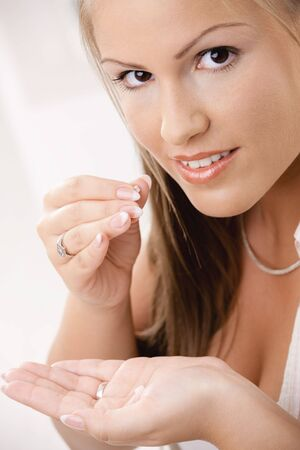 Closeup portrait of young woman girl taking pills, looking at camera. Stock Photo - 6438584