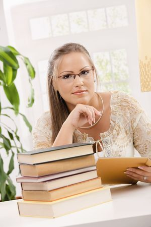 Happy student girl sitting at desk with pile of books, holding glasses, thinking. photo