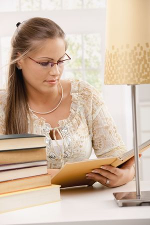 Beautiful student girl sitting at desk with pile of books, reading. photo
