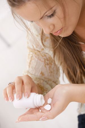 Closeup of young woman girl taking pills from bottle. Stock Photo - 6438626