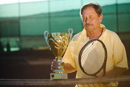 Portrait of an active senior man in his 70s on the tennis court.  photo