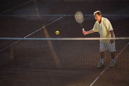 70s tennis: Active senior man in his 70s is playing tennis.  Stock Photo