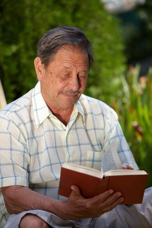 Healthy looking elderly man is his late 70s sitting in garden at home and reading book. photo