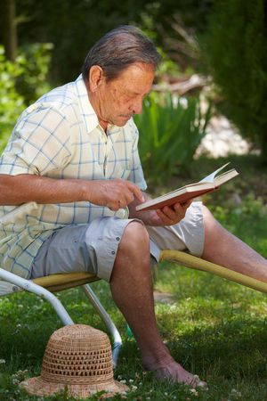Healthy looking aged man is his late 70s sitting in garden at home and reading book. photo