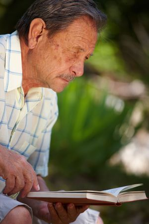 Healthy looking senior man is his late 70s sitting in garden at home and reading book, outdoor. photo