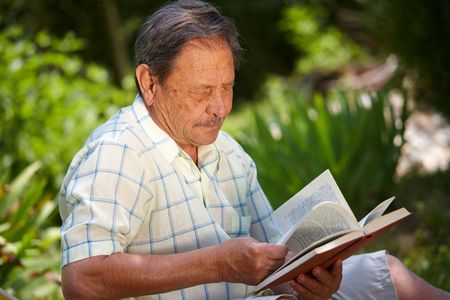 Healthy looking old man is his late 70s sitting in garden at home and reading book. photo