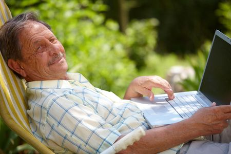 sinecure: Happy senior man is his elderly 70s sitting outdoor in garden at home and using laptop computer to browse internet, smiling.