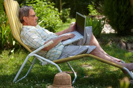 sinecure: Healthy senior man is his elderly 70s sitting outdoor in garden at home and working on laptop computer. Stock Photo