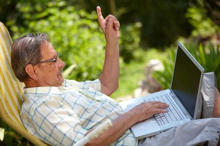 finding: Healthy senior man is his elderly 70s sitting outdoor in garden at home and using laptop computer to browse internet.